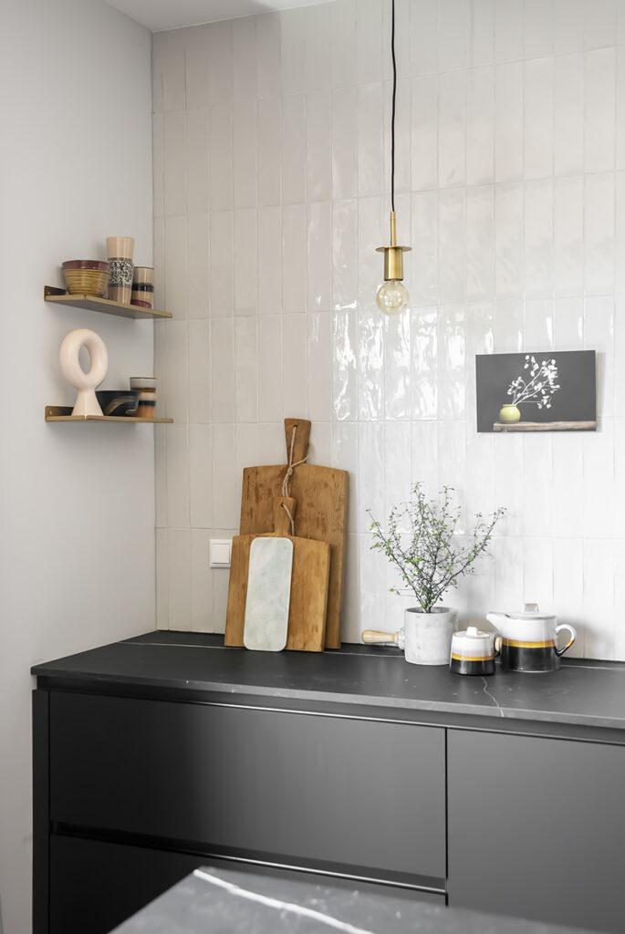 Keukenkijker in Hella's zwarte keuken met gave tegelwand